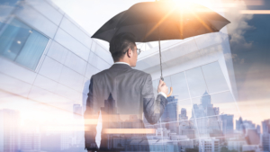 Businessmen are spreading umbrella during sunrise overlay with cityscape image. The concept of modern life